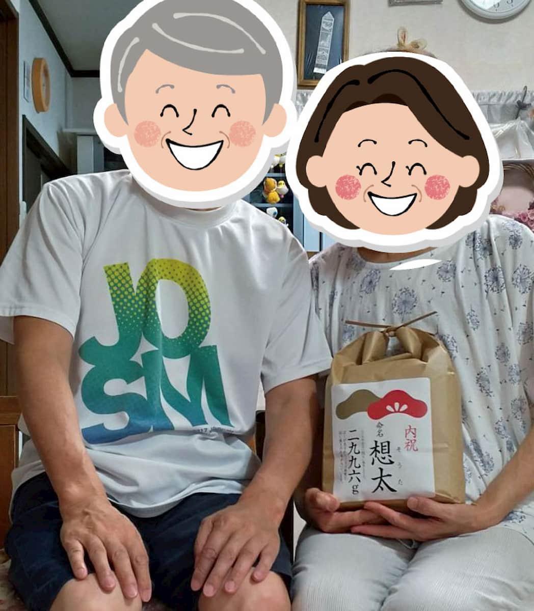 出産内祝いのお米を抱える両親
