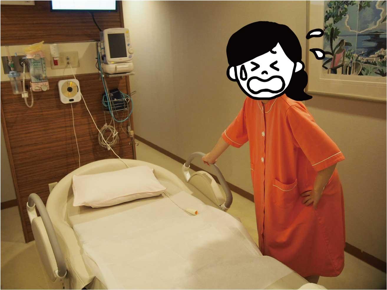 分娩室のベッドの横に立つ妊婦